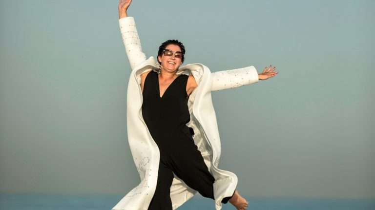 middle-aged-woman-jumping-happily-on-beach