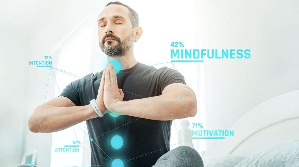 """Pleasant calm beardful man sitting on the bed closing eyes and meditating 
