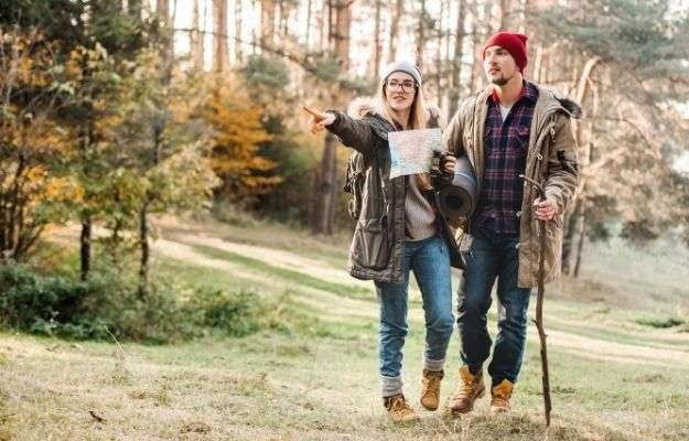 """Travel couple with map, compass and backpack in the forest 
