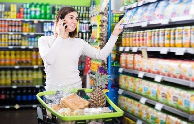 """Young female shopper talking on phone about shopping in supermarket 