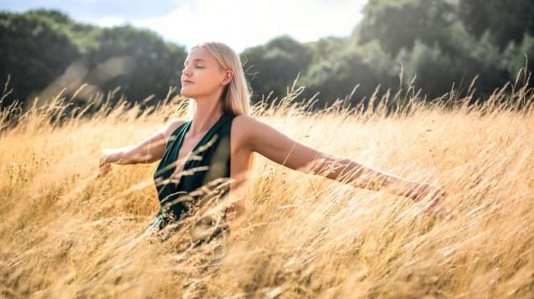 blonde-young-woman-taking-a-deep-breath-in-wheat-field