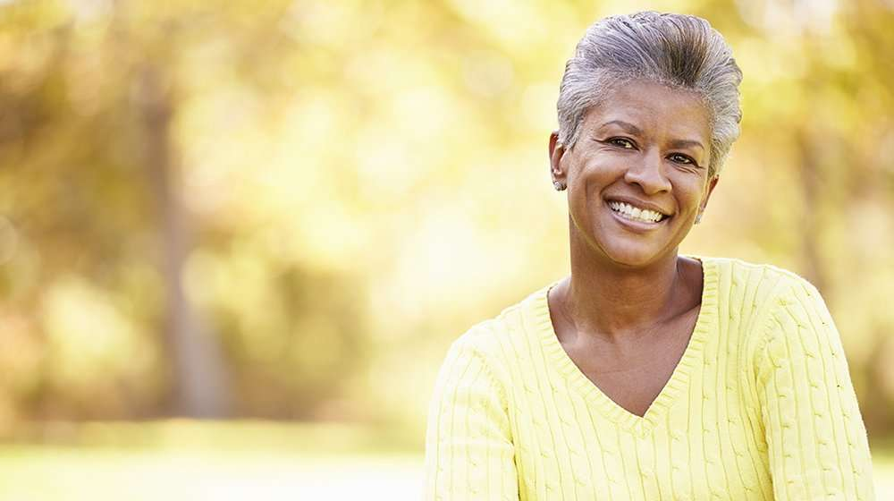Mature Woman Relaxing In Autumn Landscape | Feature Image | How to Balance Hormones as You Age