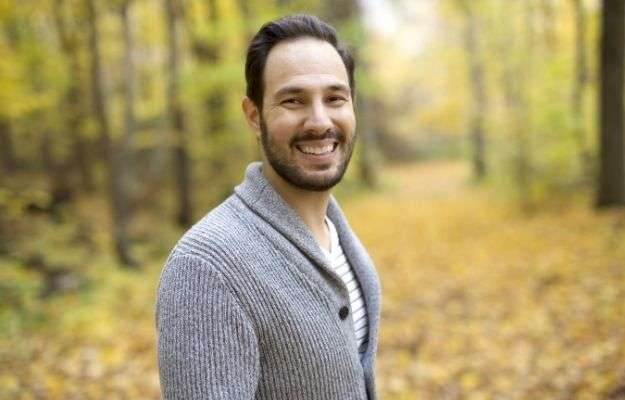 a man is smiling -and standing in the yellow leaves park | Other Benefits of 5-Amino 1MQ | Is 5-Amino 1MQ an Effective Weight Loss Peptide?
