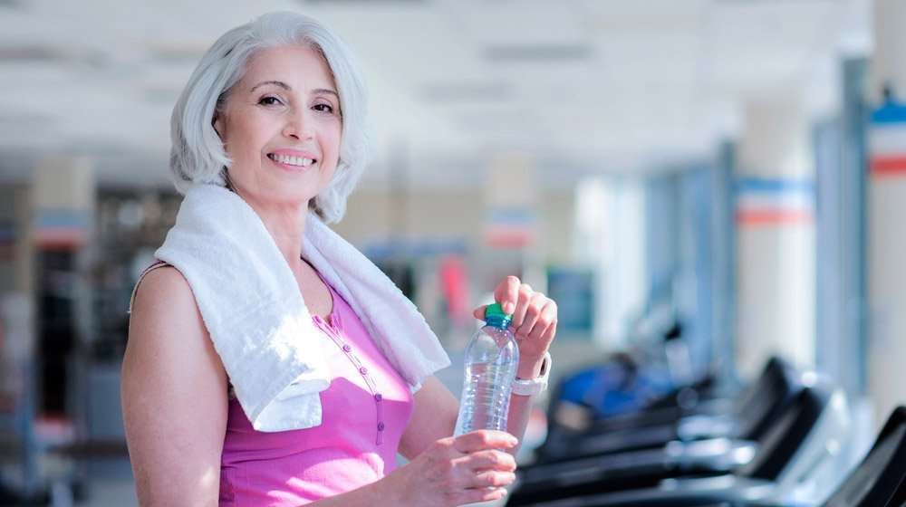 healthy-mature-woman-holding-a-bottle-of-water-after-gym-training