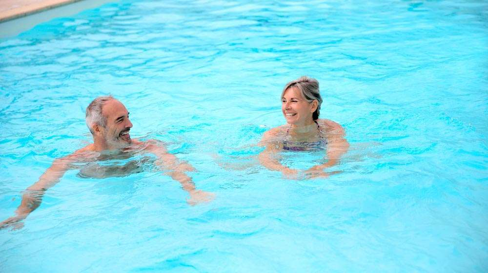 middle-aged-couple-swimming-together