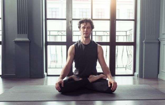 Young man meditates while practicing yoga in lotus pose | Manage Stress | 5 Ways To Deal With Receding Hairline In Men