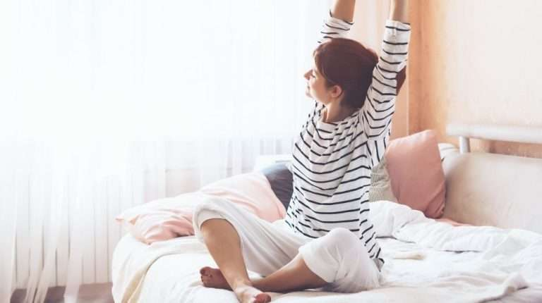 a woman sketching her arms on the bed in the morning | Feature | How to Have More Energy In the Morning