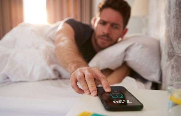 the man turns off the alarm on phone | Avoid Hitting Snooze | How to Have More Energy In the Morning