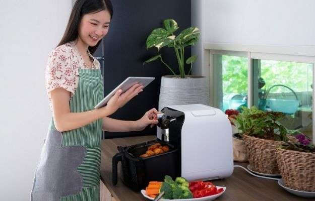 Girl using a air fryer while looking at instruction on her tablet   Buy an Air Fryer  8 Tips to SLAY 2021 and Optimize Your Health This Year
