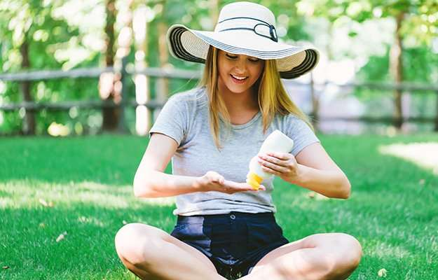 a young woman applying sun screen in the shade | You Only Need Sunscreen If It?s Sunny Outside | 6 Anti-Aging Myths & Misconceptions
