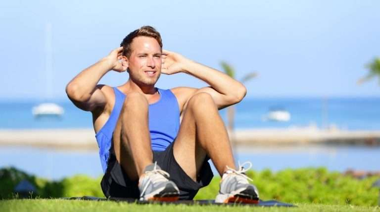 man wearing blue tanktop is doing sit-up | feature | 5 Benefits of Peptide Therapy For Targeted Health Concerns