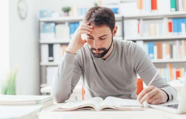 Adult focused man sitting at desk and studying at the library, learning and self improvement concept | Improved Memory