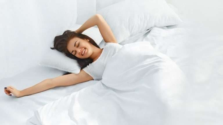 Young-beautiful-woman-waking-up-in-her-bed-fully-rested | Feature | 12 Tips for Waking Up Earlier and in a Better Mood