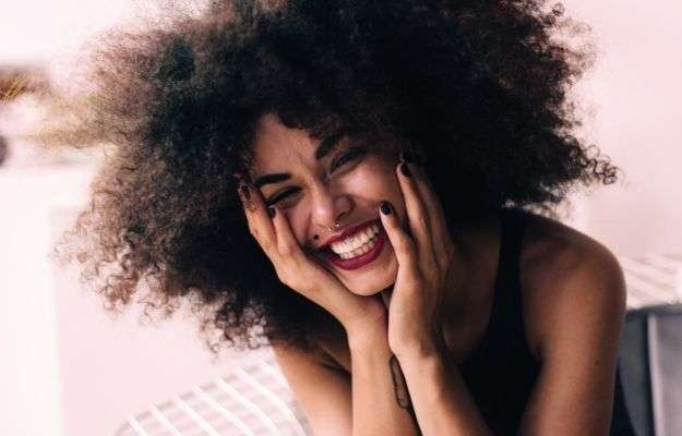 black woman smiling with hands on face