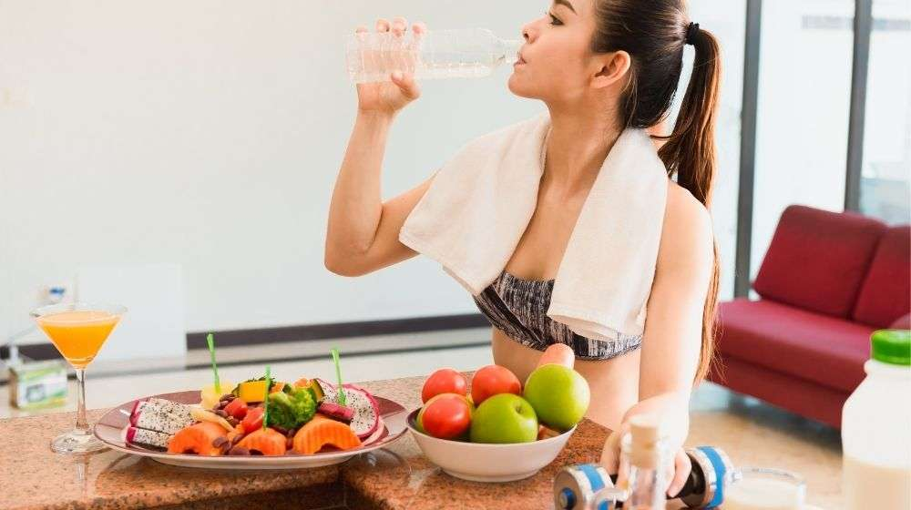 Feature | woman-drinking-water-with-dumbbel-in-her-hand-after-workout-with-salad-and-fruits-on-the-table | 7 Science-Backed Ways To Lose Stubborn Body Fat