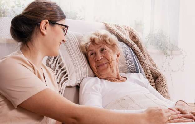 Elderly-Alzheimer-woman-in-bed-with-social-worker-helping-her | Could Testosterone Combat Dementia in Women? | HRT Could Help Dementia and Alzheimer's in Women, Studies Show
