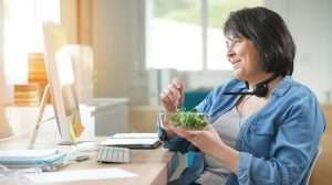 Brunette eating vegetable   Feature   Menopause Weight Gain: What It Is and How to Combat It