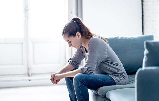 Unhappy woman sitting on the sofa and having depression | Signs and Symptoms of Estrogen Dominance