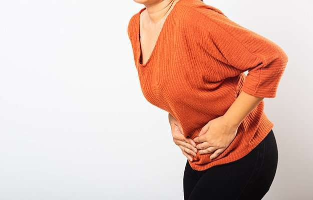 Woman in orange sweater having bloating stomach | Signs and Symptoms of Estrogen Dominance