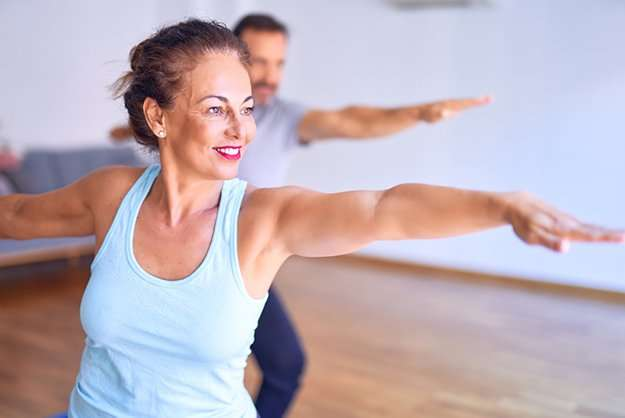 [How to Prevent Neurodegeneration] Middle age beau… practicing yoga doing warrior pose at gym_SS   Senescent Microglia Contributes To Neurodegeneration
