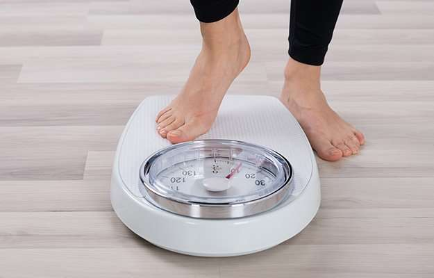person standing on white weight   How To Maintain A Healthy Weight?