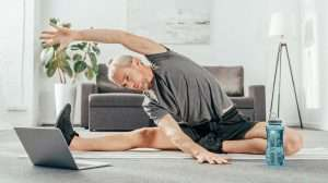 senior man doing stretching on yoga mat while looking at the laptop's screen | feature | What Is A Personalized Weight Loss Program?