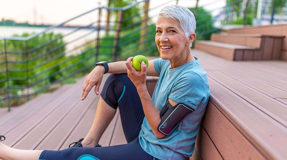 woman eating apple in her athletic outfit   feature   How To Maintain A Healthy Weight?