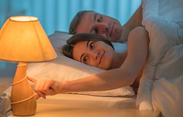 woman turning off the lamp while lying next to a man   How To Maintain A Healthy Weight?