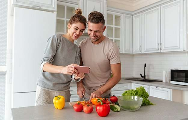 A couple smiling looking at phone and cutting vegetable | What is a Low-Calorie Diet & Who Is It For?