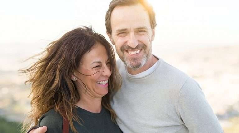 A happy middle aged couple under sunshine near the lake | Feature | What Are the Benefits of BHRT, and Is It Right for You?