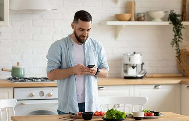 A man looking at his phone in the kitchen | What is a Low-Calorie Diet & Who Is It For?