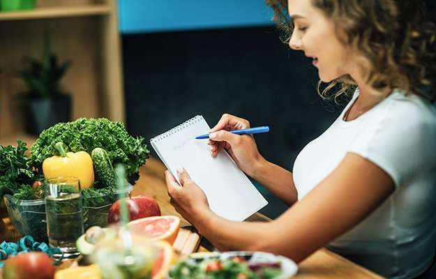 A woman writing down the calories of her food | What is a Low-Calorie Diet & Who Is It For?