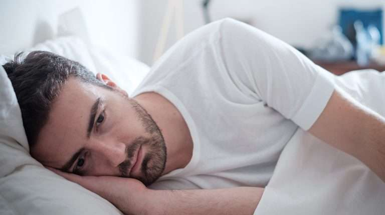 Depressed-man-lying-on-his-bed-and-feel-anxiety-ss-feat | How Do Peptides Work For Anxiety?